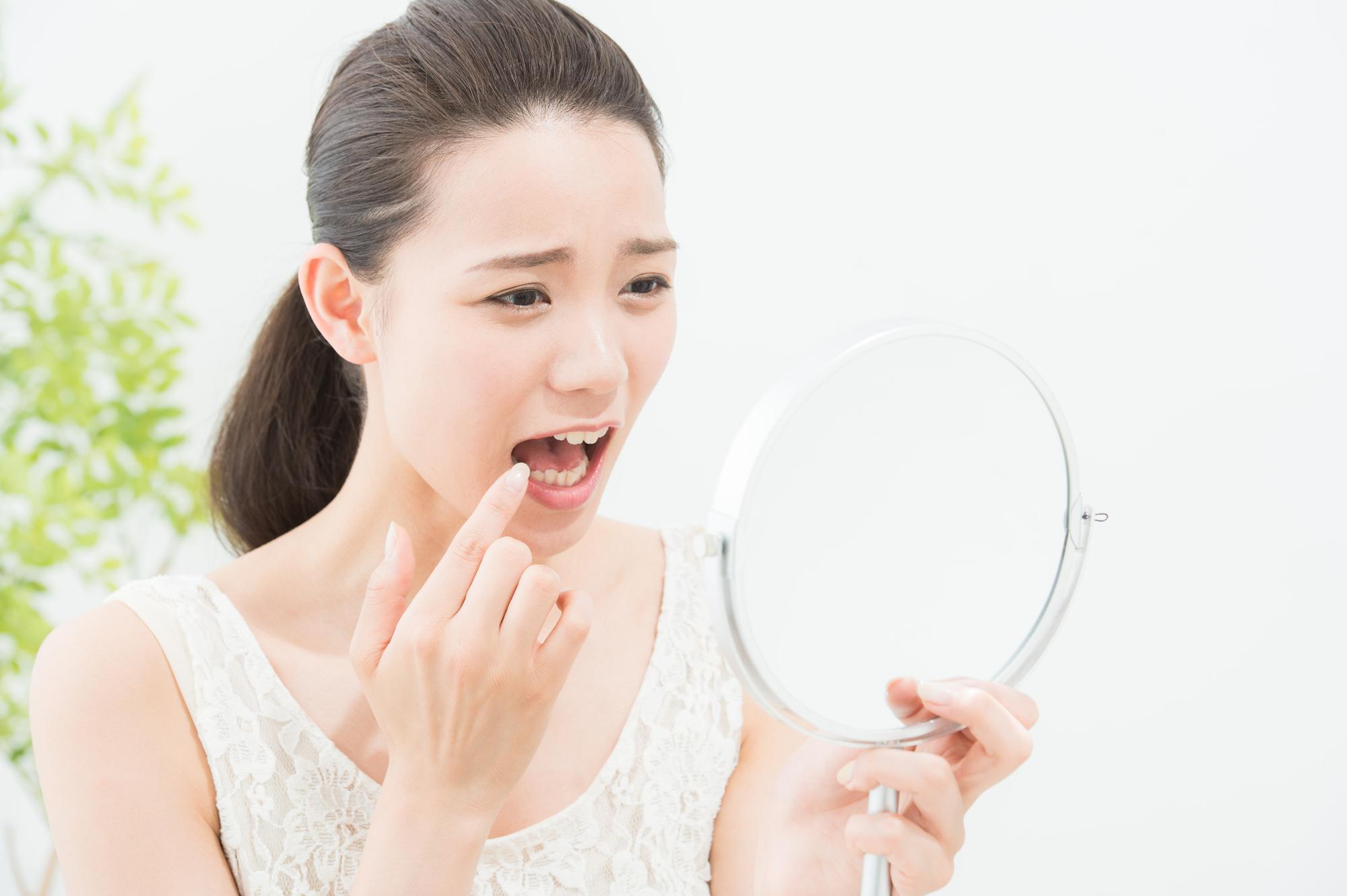 歯が痛み鏡を見る女性