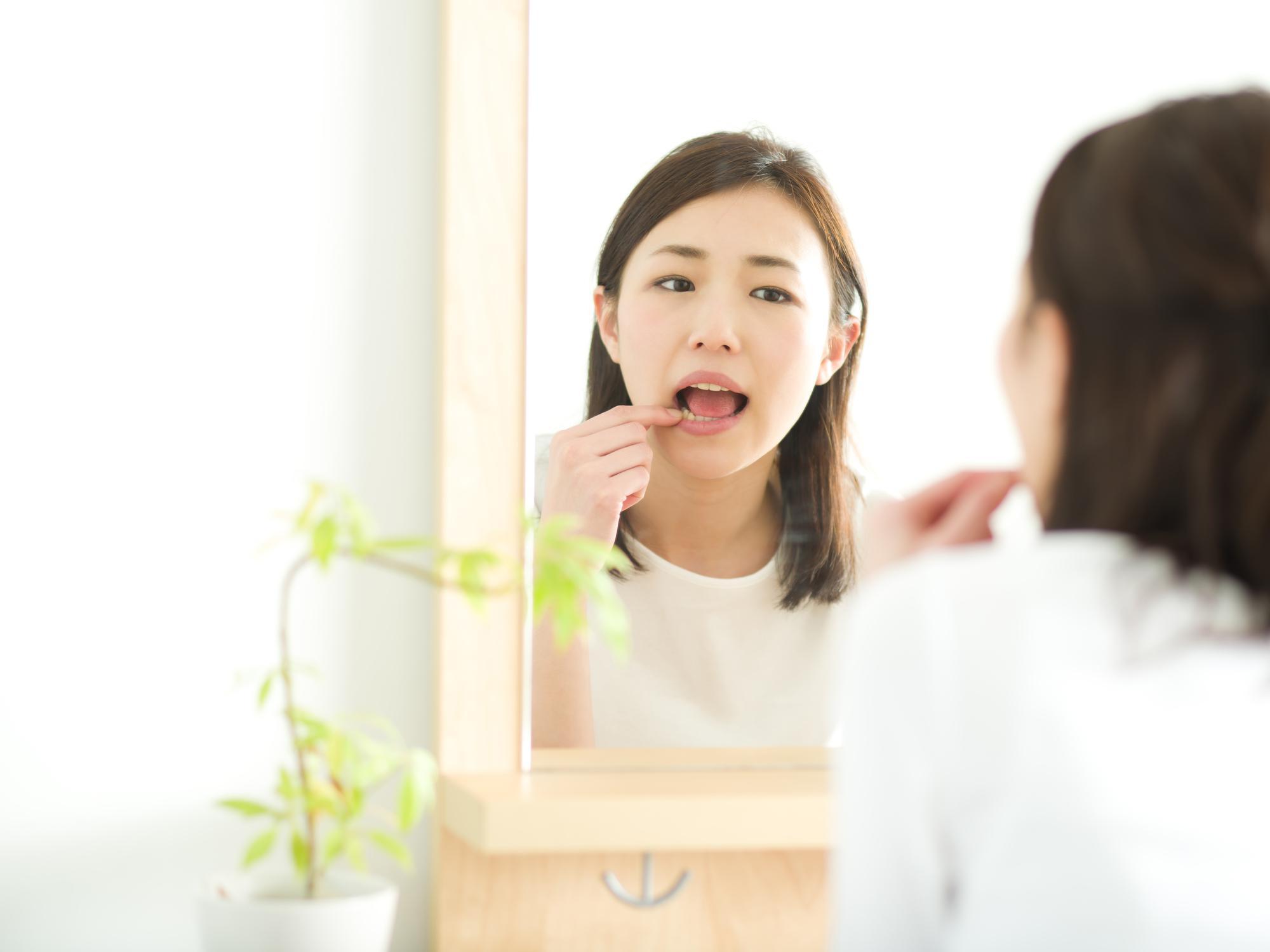 鏡で唇をチェックする女性